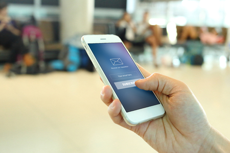 Hand holding smartphone with member loging screen on airport background