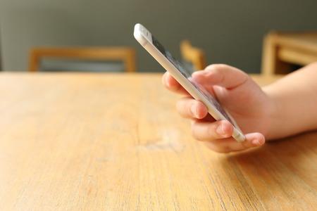 mobile phones: Hand holding mockup smartphone on desk wooden