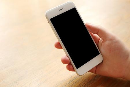 木製の机の上のモックアップのスマート フォンを持っている手 写真素材