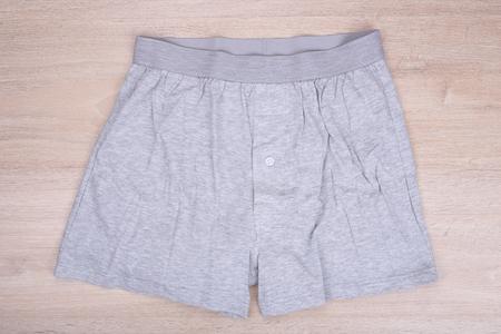 pantalones cortos: Los hombres calzoncillos grises en el fondo de madera
