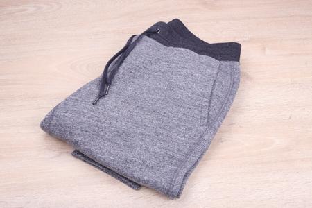 ropa deportiva: Pantalones de deporte en fondo de madera