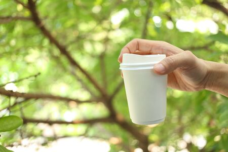 cup of coffee: Hand holding paper coffee cup with green leaves background