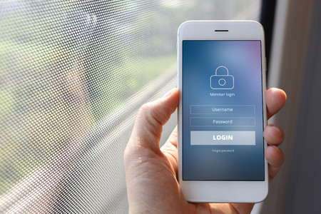 signup: Hand holding smartphone with member loging screen on train window background
