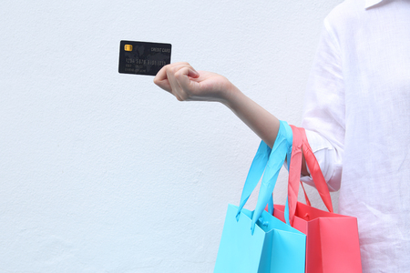 Femme tenant le panier et la carte de crédit sur fond blanc