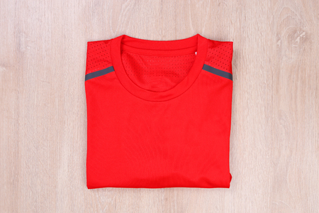 Red fold sport tshirt on wooden background