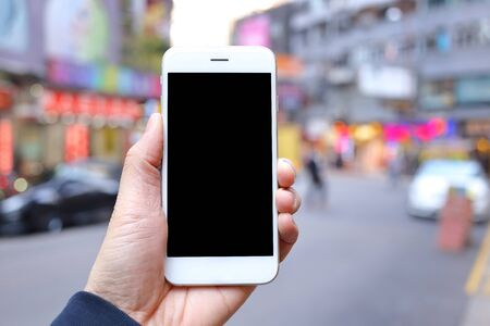 Hand holding mockup smartphone with city street background Stock Photo