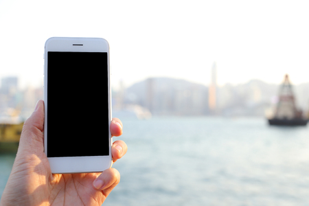 habour: Hand holding smartphone with habour and skyline background