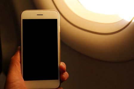 nformation: Hand holding mockup smartphone with plane window background Stock Photo