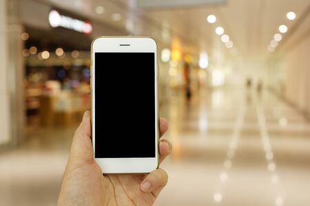 nformation: Hand holding mockup smartphone with shopping place background Stock Photo