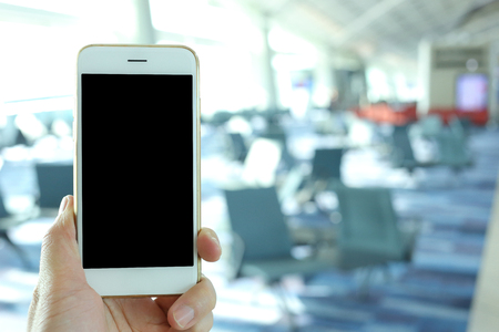 nformation: Hand holding mockup smartphone with airport passenger terminal background