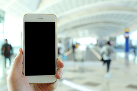 nformation: Hand holding mockup smartphone with airport passenger background