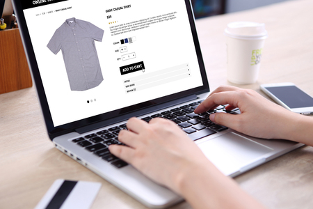 marketing online: People buying casual shirt on ecommerce website with smart phone, credit card and coffee on wooden desk