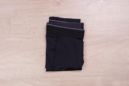 Folded tight running pants on wooden background