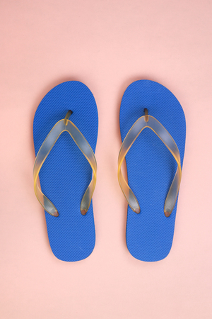 Top view blue rubber slippers on pink pastel