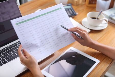 Business woman using pencil point to number on financial data sheet with laptop smartphone and office stationery on wooden desk