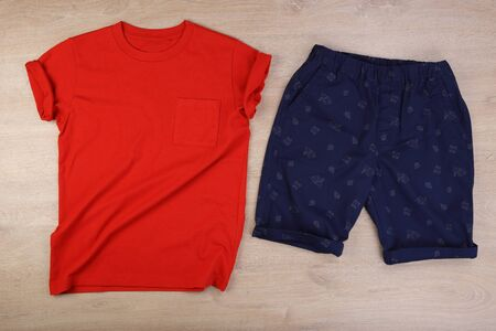 Orange wrinkled tshirt and navy blue casual short pants on wooden background