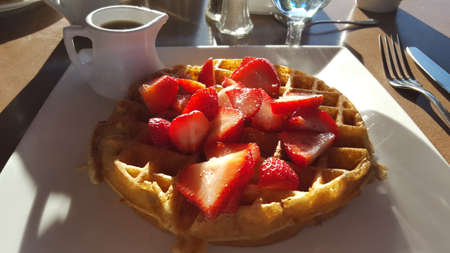 Belgian Waffle with Sliced Strawberries and Syrup Standard-Bild