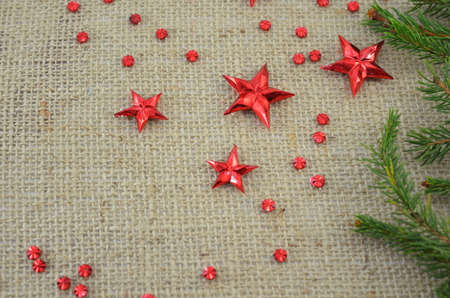 Red Christmas stars and a fir branch on a knitted table cover. photo