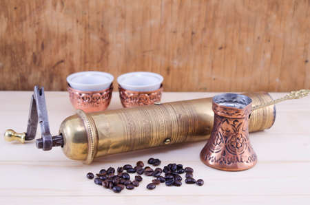 Retro coffee grinder and a Turkish coffee set on a wooden table photo