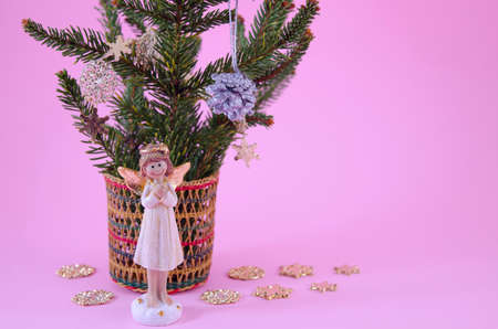 Angel figurine and star decorated fir branches on pink photo