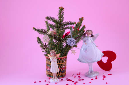 Two angel figurines on pink background, decorated with stars and a fir tree photo