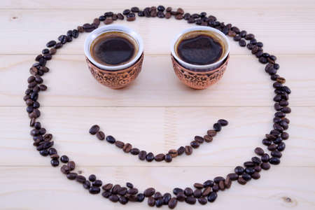coffee grains: Smiley made out of coffee grains and two vintage cups of coffee as eyes Stock Photo
