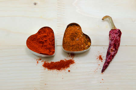 scattered in heart shaped: Two pepper hearts and a dried paprika on a wooden table