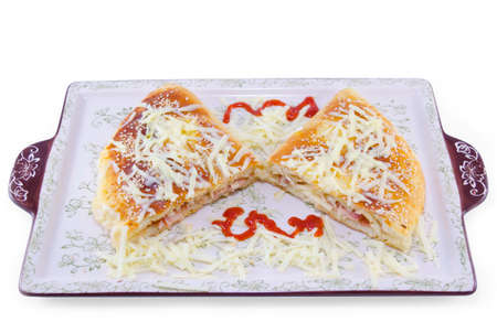 Stuffed pizza cut in half decorated with grated cheese on a plate, isolated on white background photo