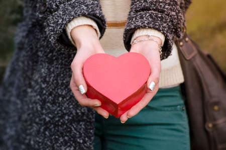 Gentle womans hands holding a heart shaped box, shot outdoors photo