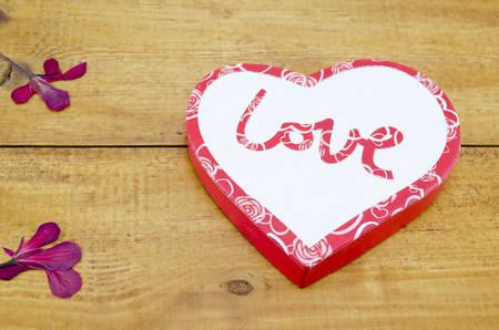 flores secas: Caja en forma de coraz�n en una mesa de madera decorado con flores secas