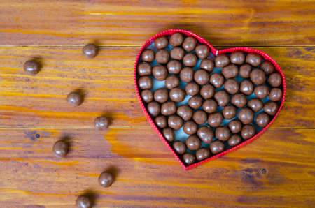 scattered in heart shaped: Heart shaped box filled with small chocolates balls with a lot of them scattered on the wooden table