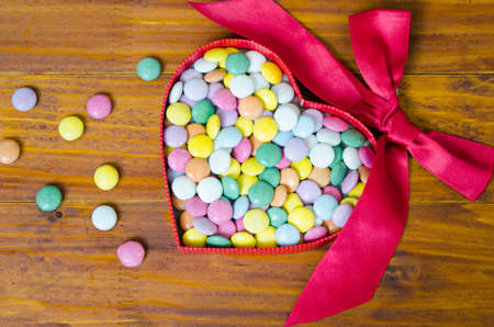 scattered in heart shaped: Colorful chocolate pills in a heart shaped box
