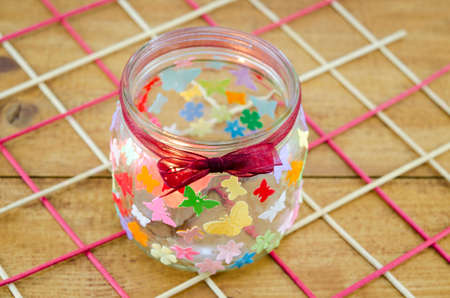 original idea: DIY candleholder decorated with colorful butterflies on a wooden table Stock Photo