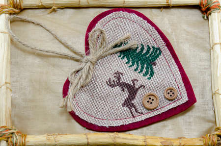 Handmade Christmas heart embroidery in a vintage bamboo frame Stock Photo