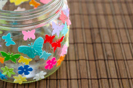 candleholder: Closeup of a DIY candleholder decorated with colorful butterflies on a wooden table Stock Photo