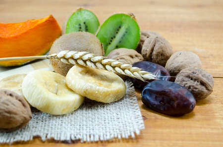 kiwis: Dried figs, palms, pumpkins with walnuts and kiwis on a wooden table