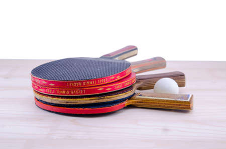 tabletennis: Bunch of old table tennis rackets and a table tennis ball on a table isolated Stock Photo