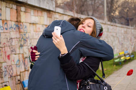 Boy hugging a girl while she looks at her smartphone outdoors