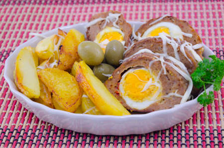 Delicious meatloaf, potato and olives on a restaurant dining table
