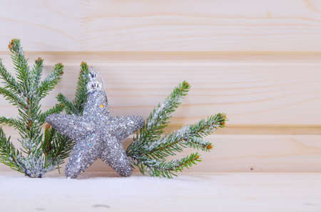 A shiny star ornament with fir branches on a wooden suface covered with snow