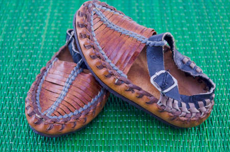 bast: Serbian peasant shoe on green tablecloth Stock Photo