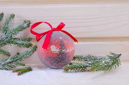 imbedded: Red vintage Christmas ornament with a fir tree imbedded on a wooden background