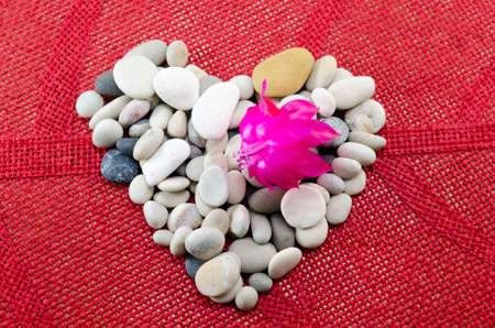 red pebble: Pebble heart decorated with a beautiful pink flower on red tablecloth