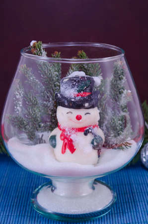 glass vase: Toy snowman in a glass vase covered with snow against a blue background Stock Photo