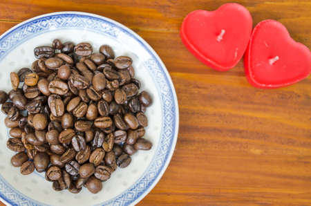 Coffee beans on a old plate, with heart shaped candles on a wodeen table Stock fotó