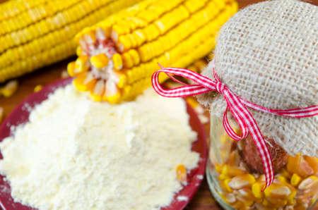 corn ear: Un frasco con el ma�z, la harina y el o�do de ma�z sobre una mesa de madera Foto de archivo