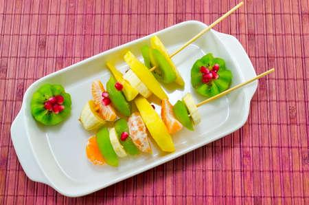 kiwis: Two skewers full with colourful kiwis, bananas, oranges, pomegranade
