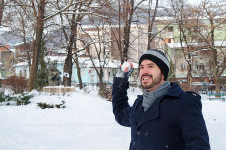 Young man throwing a snowball in a snow covered park Stock Photo