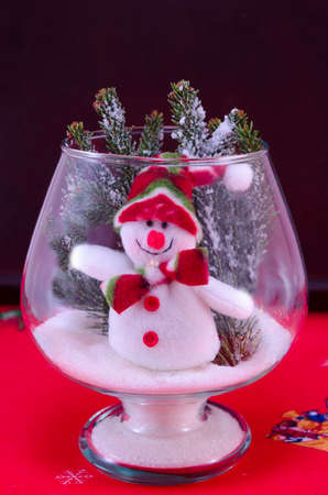 red tablecloth: Toy snowman in a glass vase decorated with fir brances on a red tablecloth