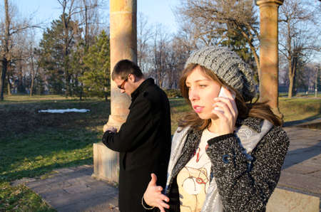 waiting phone call: Girl talking on the phone while the boy is waiting in a park outdoors